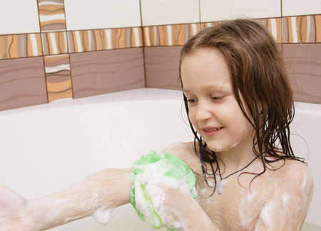 smiling little child covered with a soap at the bath