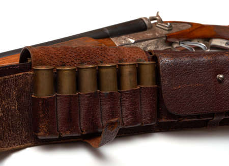 hunting belt with a cartridges and the rifle lying beside