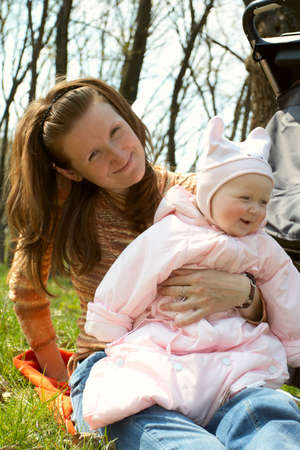 perambulator: smiling mother with baby sitting on a grass outdoor