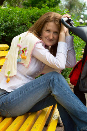 perambulator: young mother with perambulator sitting on a bench at the park  Stock Photo