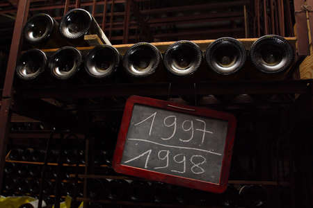 nameboard: lot of bottles keeping at the dusk cellar with the nameboard witn the year of crop