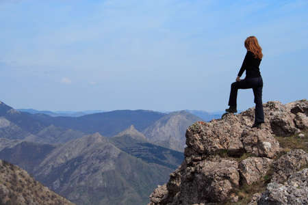 girl standing at the edge of rock