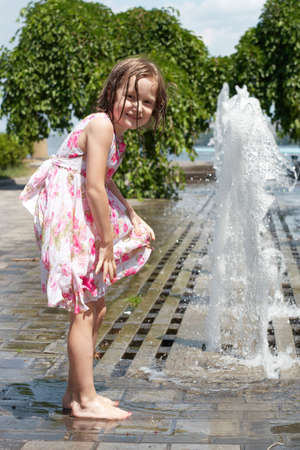 wet clothes: young girl enjoys a summer playing at the park fountain