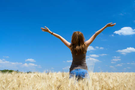young girl joys on the wheat field at the bright sunny day
