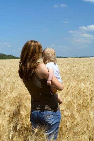 la tenue d'une mère à l'enfant un champ de blé Banque d'images