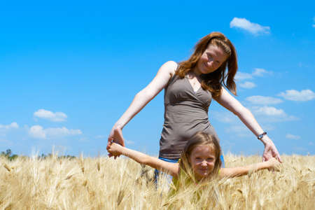 mother holding a hands of daughter at the wheat field