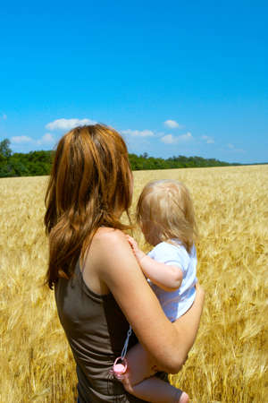 mother holding a child at the wheat field Stock Photo - 5313287