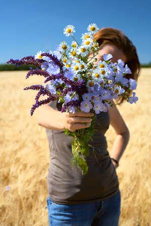 girl gives you a bunch of field flowers. Focus on a bouquet. Small DOF  photo