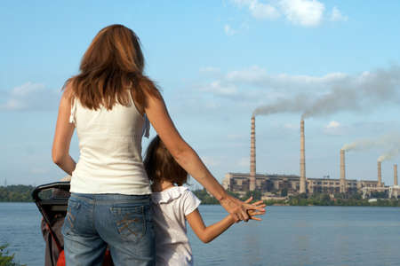 polluting: care future concept. Young mother with her kids are looking at the chimney-stalks polluting an air