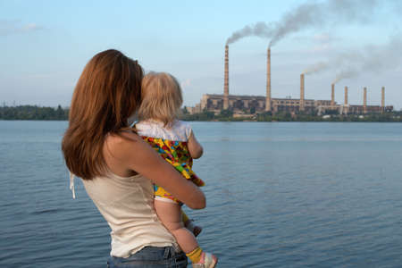 care future concept. Young mother with her kids are looking at the chimney-stalks polluting an air