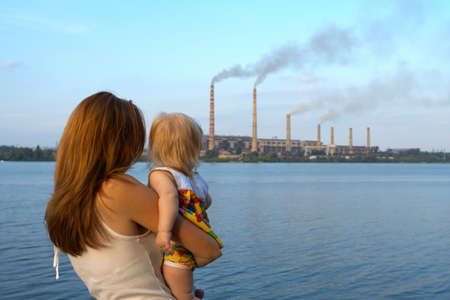 care future concept. Young mother with her kids are looking at the chimney-stalks polluting an air Standard-Bild