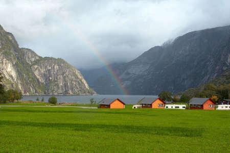 pré vert avec des maisons sur une côte du fjord et montagnes avec arc-en-ciel dans la distance, Norvège