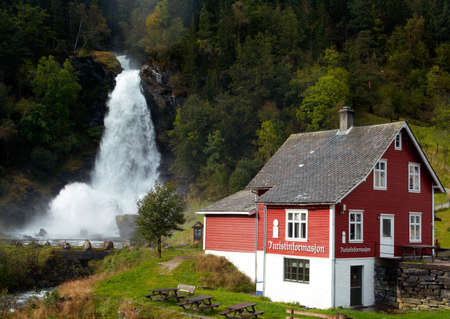 traditional norwagian wooden house and  waterfall in the distance  photo