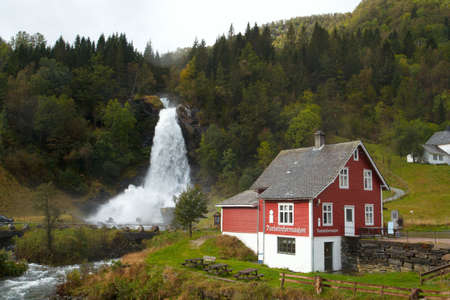traditional norwagian wooden house and  waterfall in the distance