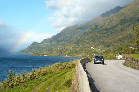 long range: alone car on a sunny road at fjord coastline