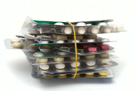 tightened: batch of packages of multicolored pills tightened by the elastic band  Stock Photo