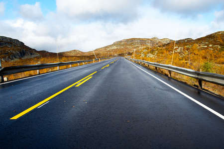 receding: empty mountain road road receding into the distance at the cloudy autumn day  Stock Photo