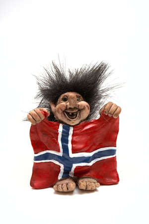 norwegian: figurine of smiling troll hanging a flag at his arms isolated on a white, norway