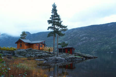 traditional norwegian wooden house standing at the lakeside and mountains in the distance Stock Photo - 6063757