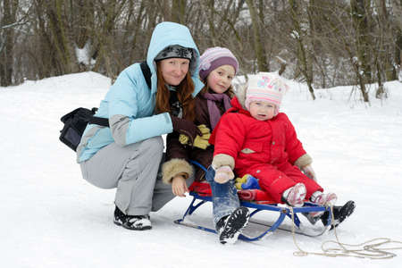 mother with smiling daughters on a winter walk