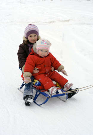 winter walk - little girls sitting on a sledge