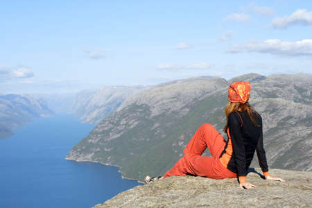 scandinavian people: girl hiker sitting on a brink rock and looking at the mountains