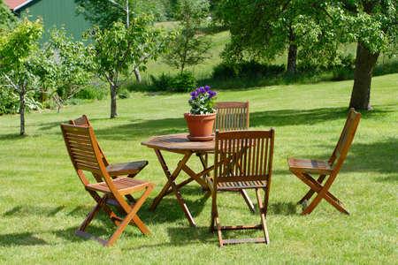 table et chaises, debout sur une pelouse dans le jardin.