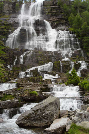 large cascade waterfall in the summer woods, norway