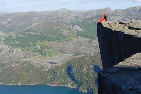 brink: girl hiker sitting on a brink rock Preikestolen and looking at the mountains