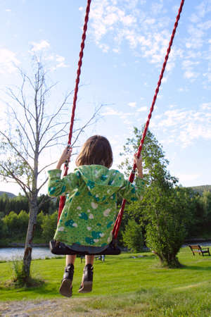 little girl rolling on a swing at the park