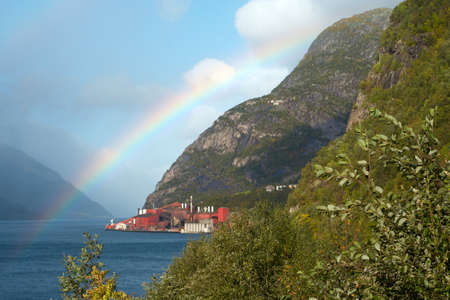 factory to stand at the coast fjord and mountains with rainbow in the distance,norway  photo