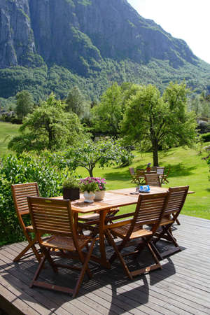 table and chairs standing at the garden and mountains in the background Standard-Bild