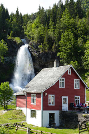 traditional norwegian wooden house  with waterfall in the distance