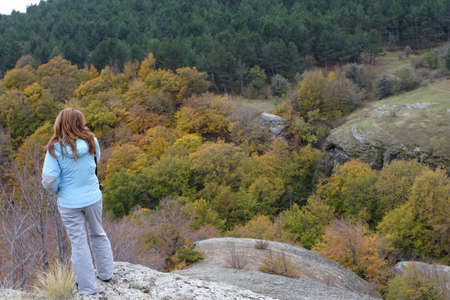 girl standing on the rock and looking at autumn forest Stock Photo - 8111305