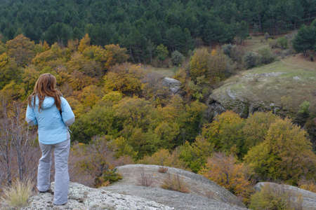 girl standing on the rock and looking at autumn forest Stock Photo - 8111306