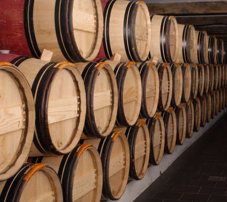 group of oak barrels with the wine at the cellar  photo