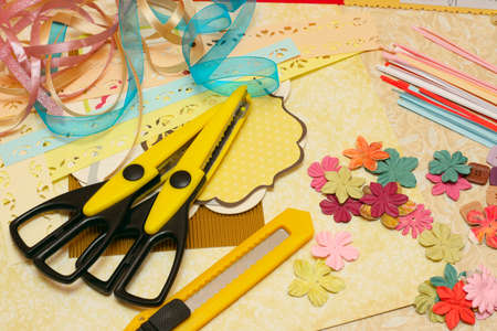 paper cutting: hand made scrapbooking post card and tools lying on a table  Stock Photo