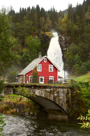 traditional norwegian wooden house  with waterfall in the distance. Waterfall Steindalsfossen, Norway  photo