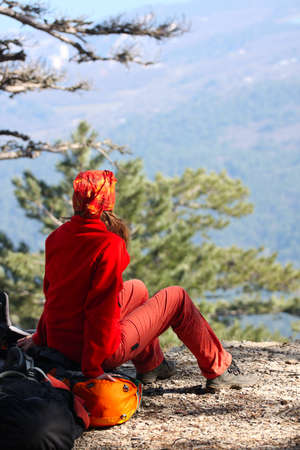girl hiker sitting on a rock and looking at the mountains Stock Photo - 9461603