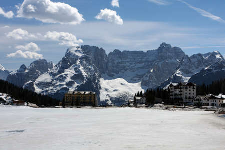 large frozen mountain lake with snowed mountains in the background, italy dolomites