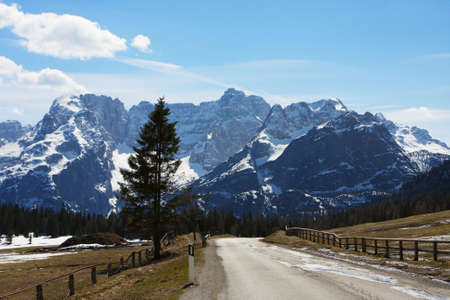 empty winding road to the high snowed mountains  photo