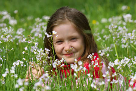 smiling child girl lying on a grass at the meadow. Stock Photo - 9683263