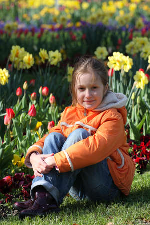 smiling child girl sitting on a grass at the park. Stock Photo - 9683266