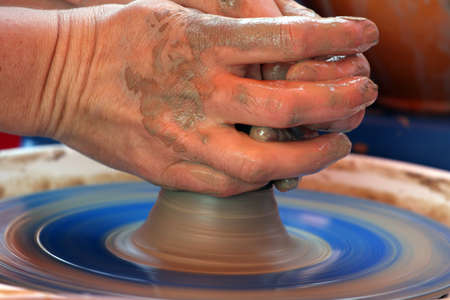 human hands moulding with the clay on a potter`s wheel close up. photo