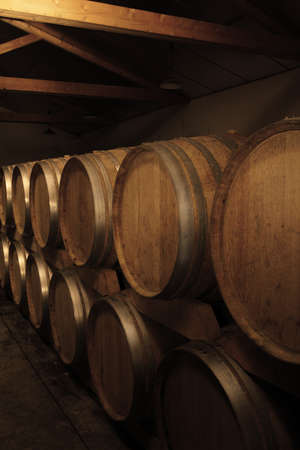 group of oak barrels with the wine at the cellar. Stock Photo