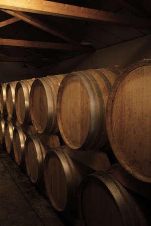 Groupe des tonneaux de chêne avec le vin à la cave.