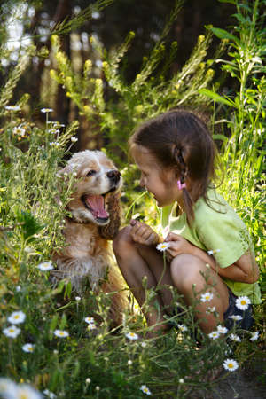 little girl and the dog sitting at the grass  photo