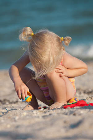 blonde little girl: little girl joys with her toys on a beach. Stock Photo
