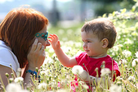 mother with baby outdoor on a grass at the spring park. Stock Photo - 10264851
