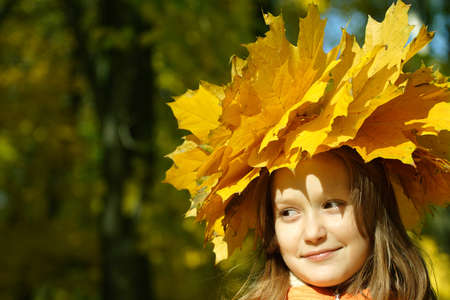 young girl at the park with diadem from yellow maple leaves. photo